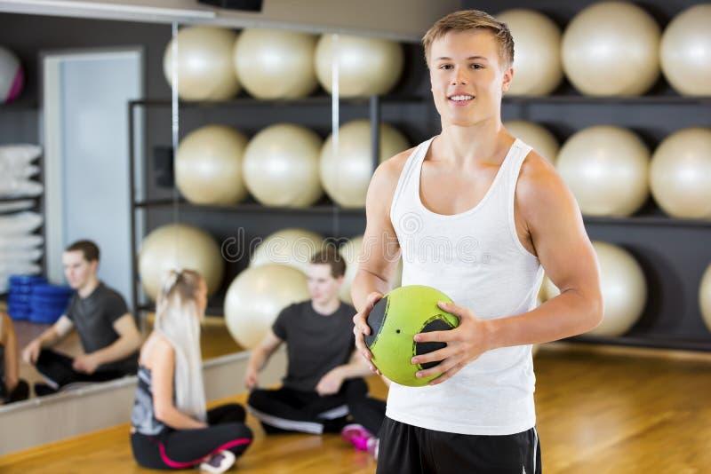 Homme sûr tenant le medicine-ball tandis qu'amis se reposant dans le gymnase image stock