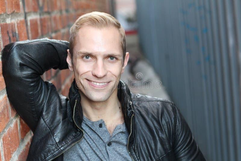 Homme saisissant souriant et se penchant sur un mur avec l'espace de copie photographie stock libre de droits