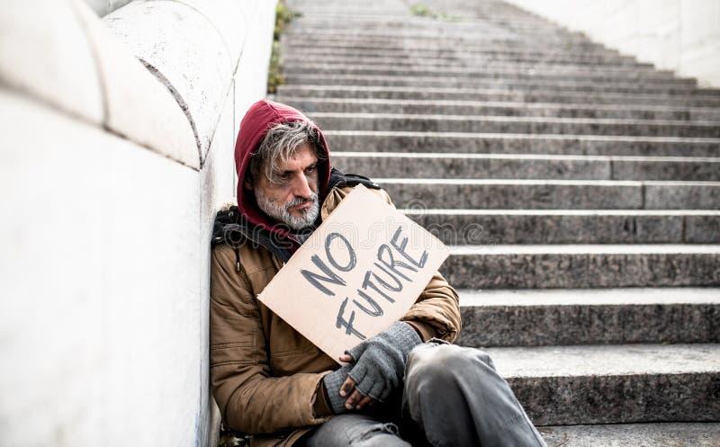Homme sans abri de mendiant s'asseyant dehors dans la ville ne tenant aucun futur signe de carton images stock