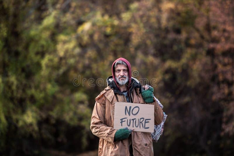 Homme sans abri de mendiant se tenant dehors en parc, tenant le signe de sac et de carton photographie stock