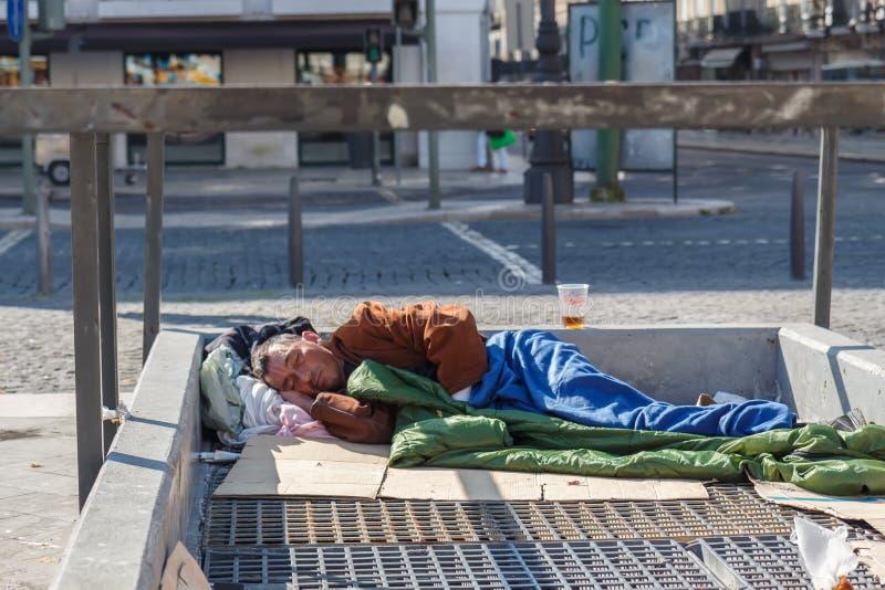Homme sans abri dormant sur l'évent de la métro photo libre de droits