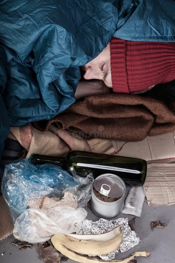 Homme sans abri parmi des déchets photo stock