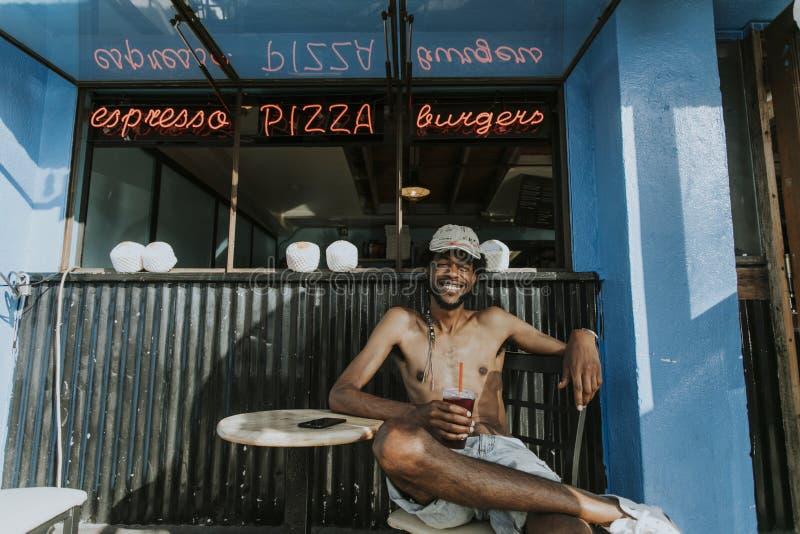 Homme sans chemise s'asseyant à un café photographie stock