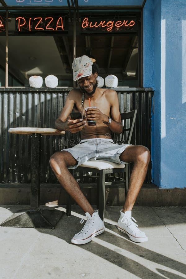 Homme sans chemise s'asseyant à un café images libres de droits