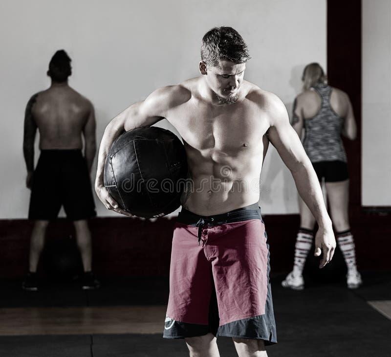 Homme sans chemise tenant le medicine-ball dans le gymnase photo libre de droits