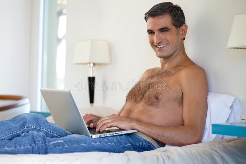 Homme sans chemise travaillant sur l'ordinateur portable photos libres de droits