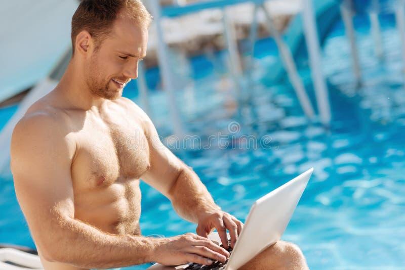 Homme sans chemise travaillant sur l'ordinateur portable près d'une piscine images libres de droits