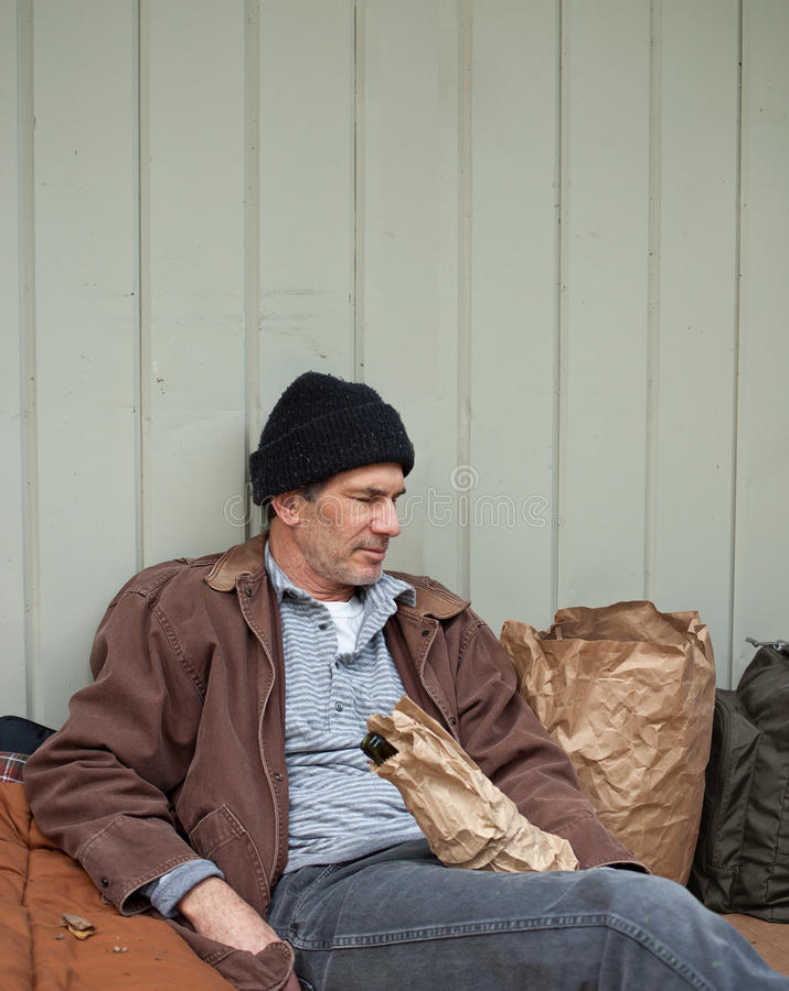 Homme sans foyer avec des affaires sur la rue photo libre de droits
