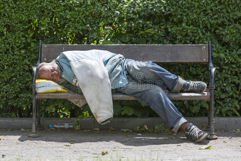 Homme sans foyer dormant sur un banc photos stock