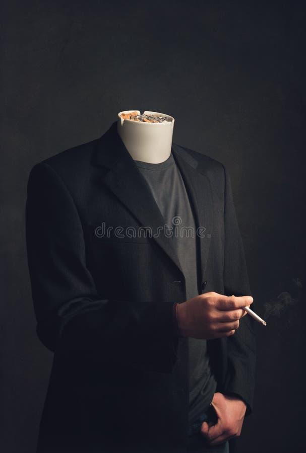 Homme sans tête avec le cendrier fumant une cigarette photo libre de droits
