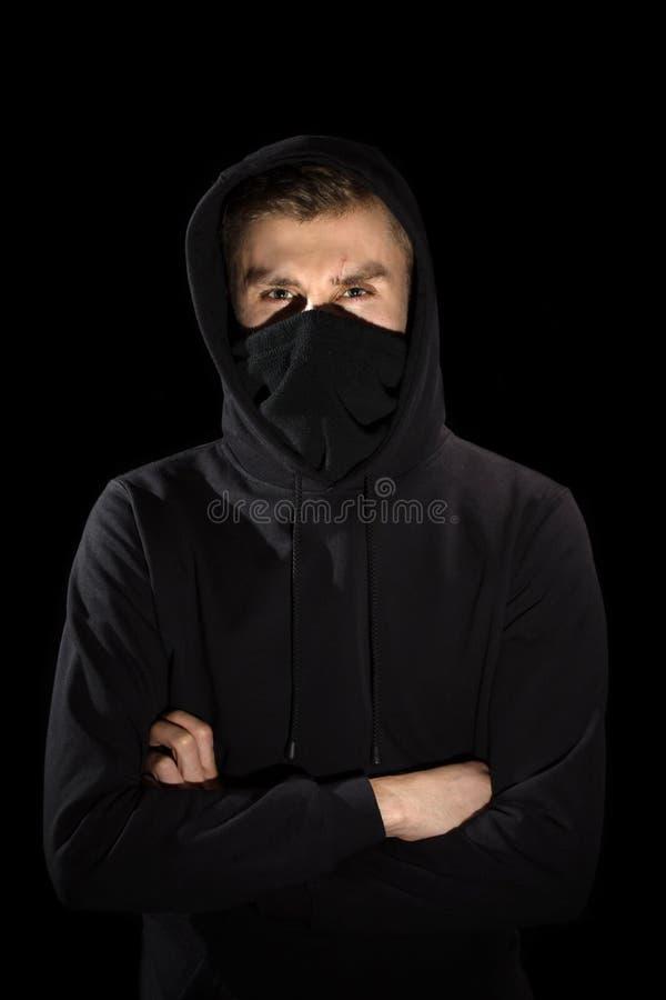 Homme sans visage avec les yeux ouverts dans le hoodie se tenant sur le noir images libres de droits