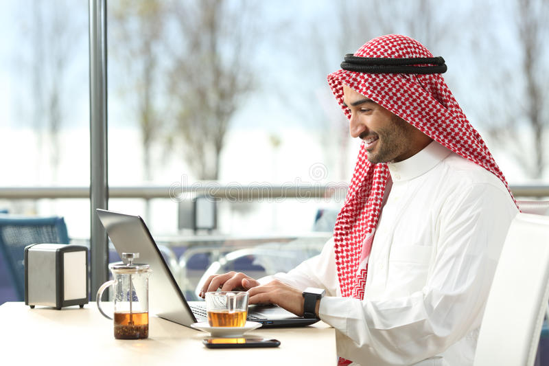 Homme saoudien arabe travaillant en ligne avec un ordinateur portable photographie stock libre de droits