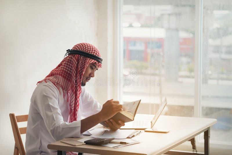 Homme saoudien arabe travaillant en ligne avec un ordinateur portable et un livre de lecture dedans photos stock