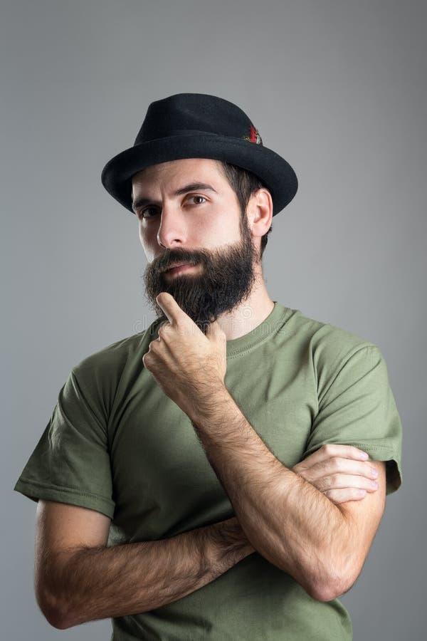 Homme sceptique méfiant touchant sa barbe regardant l'appareil-photo image stock
