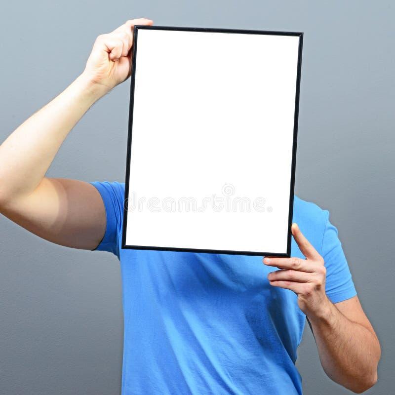 Homme se cachant derrière le panneau vide de signe photos stock
