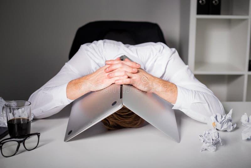 Homme se cachant sous l'ordinateur portable photographie stock