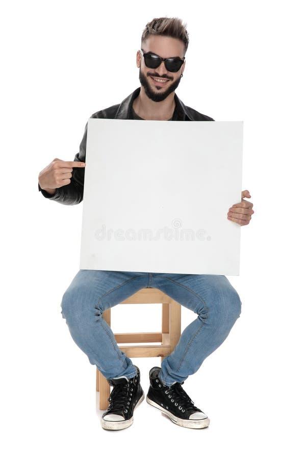 Homme se dirigeant pour masquer le panneau d'affichage tout en souriant photo libre de droits