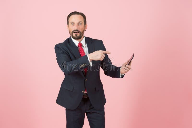 Homme se dirigeant sur le Smart-téléphone et le visage étonné Le directeur barbu a très étonné à l'information du message photo libre de droits