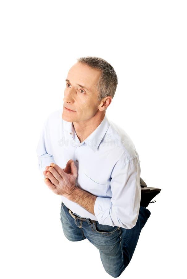 Homme se mettant à genoux et priant à Dieu images stock