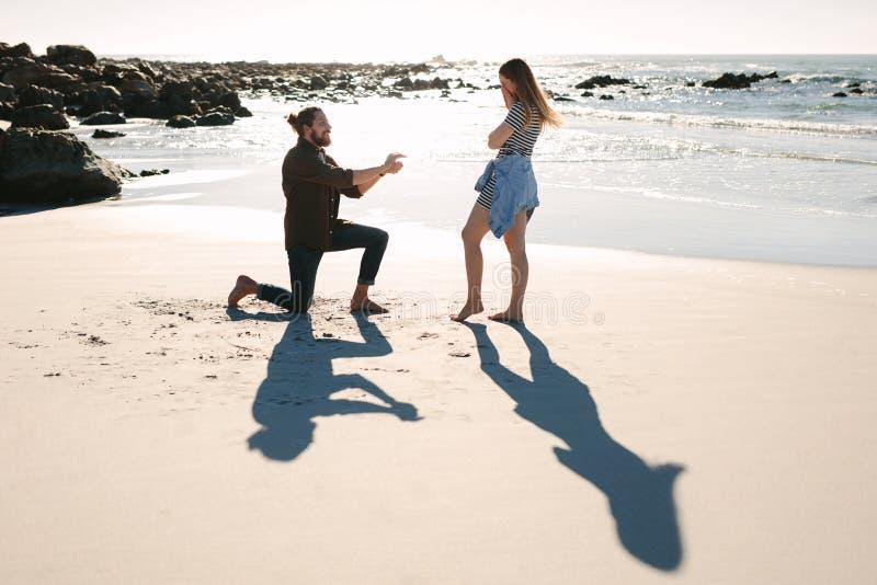 Homme se mettant à genoux et proposant à la femme par la mer images stock