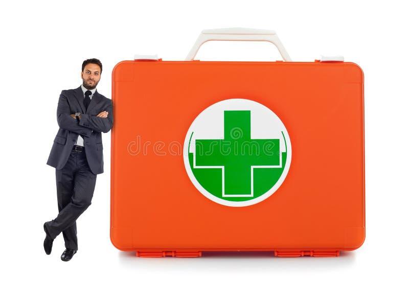 Homme se penchant contre près de la boîte de premiers secours photographie stock libre de droits