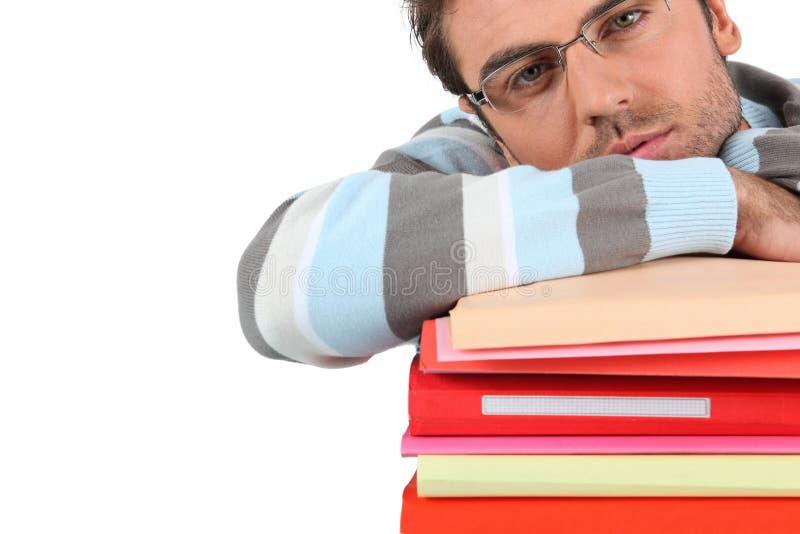 Homme se penchant sur des livres image stock