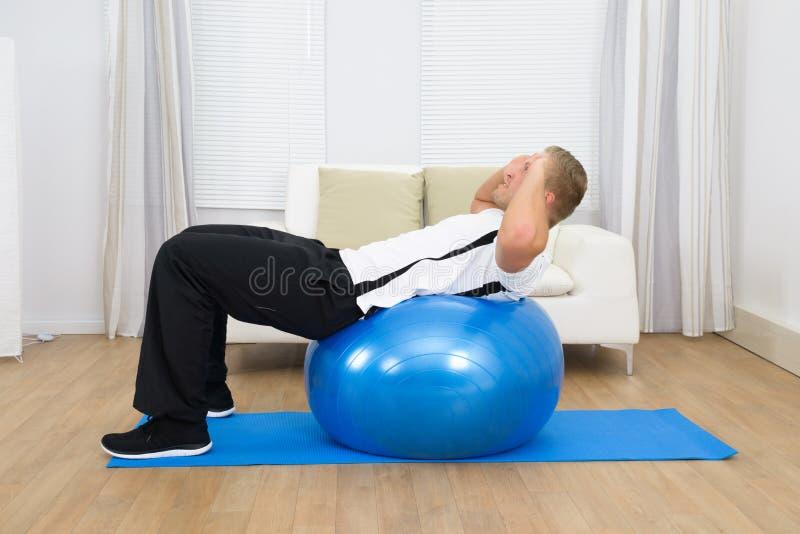 Homme se penchant sur la boule de pilates faisant l'exercice photos stock
