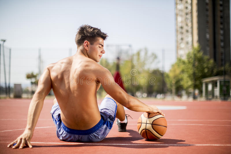 Homme se reposant de jouer le basket-ball photo libre de droits