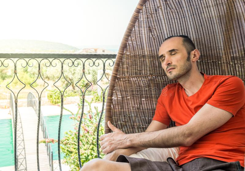 Homme se reposant pour détendre sur la chaise de oscillation dans un balcon photo libre de droits