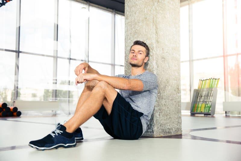 Homme se reposant sur le plancher au gymnase photographie stock libre de droits