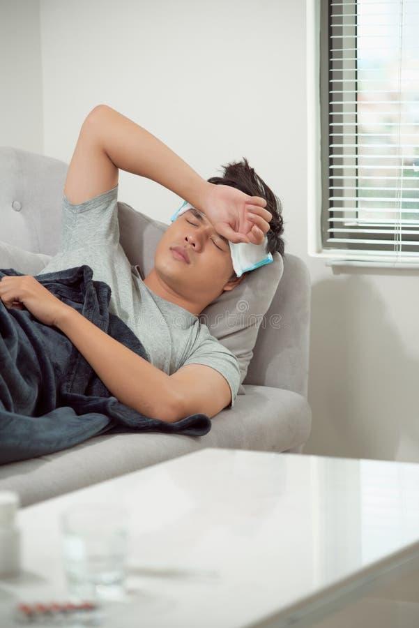 Homme se sentant froid, se situant dans le sofa et soufflant son nez image stock