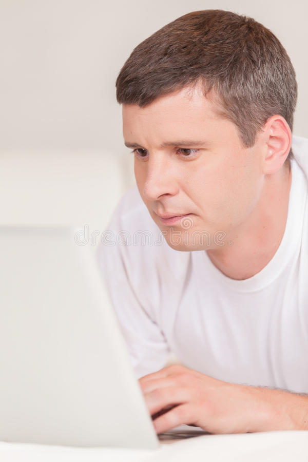 Homme se situant dans le lit avec son ordinateur portable photo stock