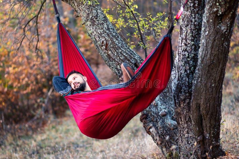 Homme se situant dans un hamac et détendant dehors photos libres de droits