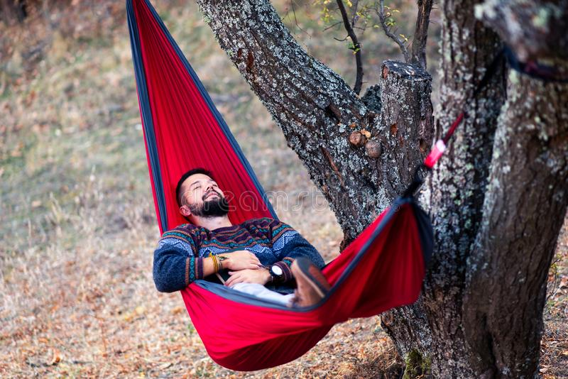 Homme se situant dans un hamac et détendant dehors photographie stock