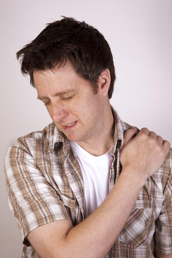 Homme se tapissant de la douleur tenant son épaule images stock