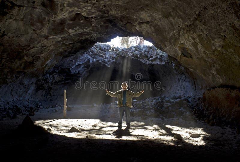 Homme se tenant dans des rayons de soleil de caverne photographie stock