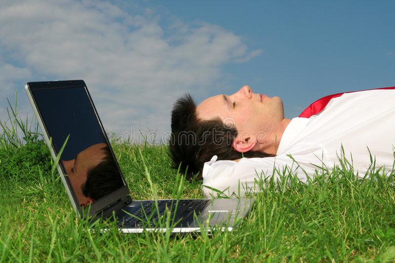 Homme se trouvant sur l'herbe photographie stock libre de droits