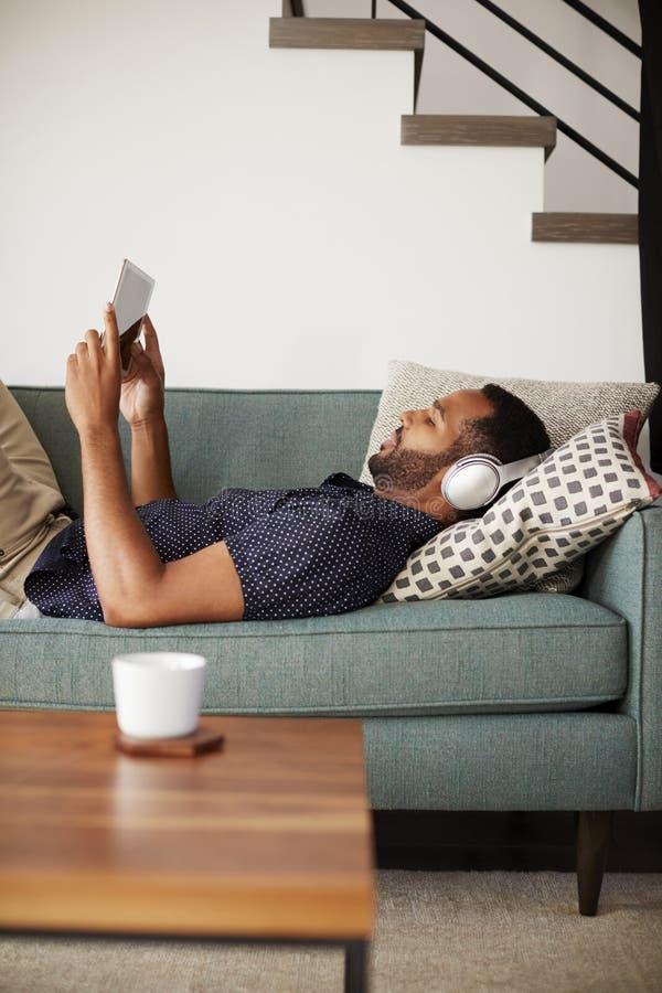 Homme se trouvant sur Sofa At Home Wearing Headphones et le film de observation sur la Tablette de Digital images stock