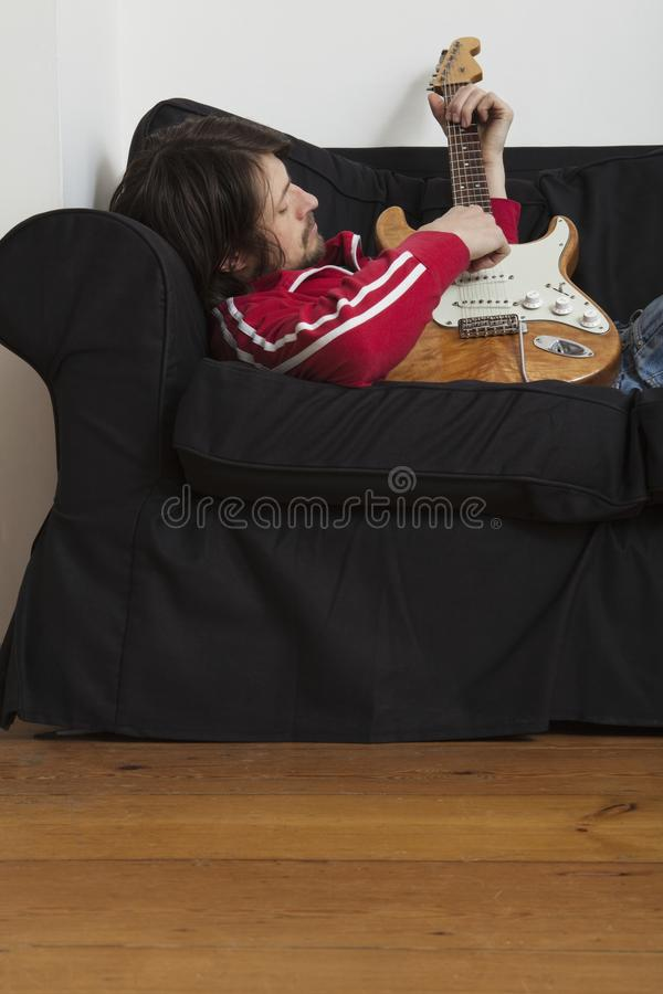 Homme se trouvant sur Sofa And Playing Guitar image stock