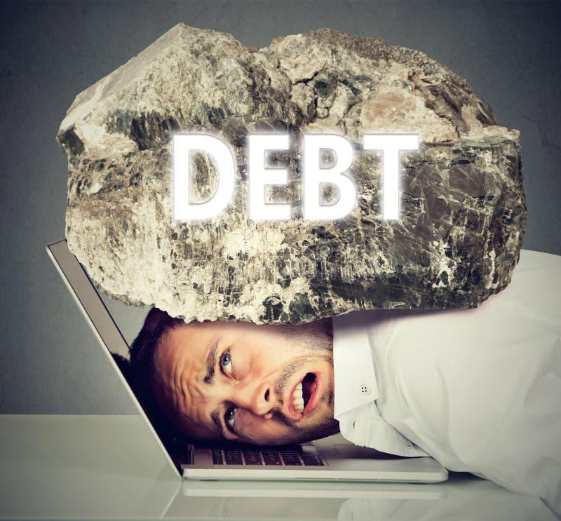 Homme serré entre l'ordinateur portable et la roche Concept de dette d'emprunt d'étudiant images libres de droits