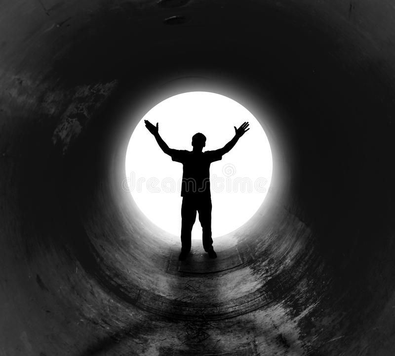 Homme seul à l'extrémité du tunnel foncé image libre de droits