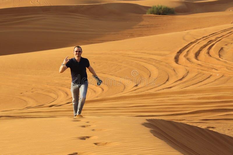 Homme seul marchant dans le désert ensoleillé photo stock