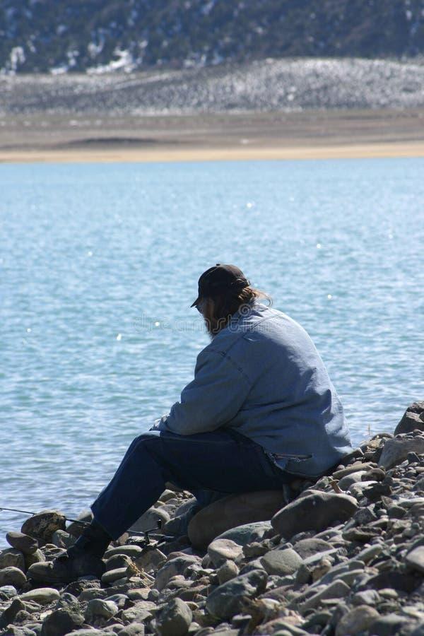 Homme seul par le lac photos stock