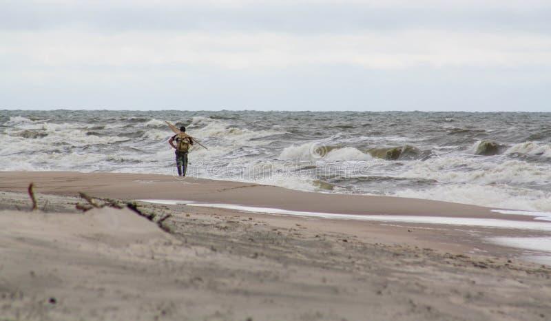 Homme seul sur la plage Rassemblement ambre, temps orageux photographie stock