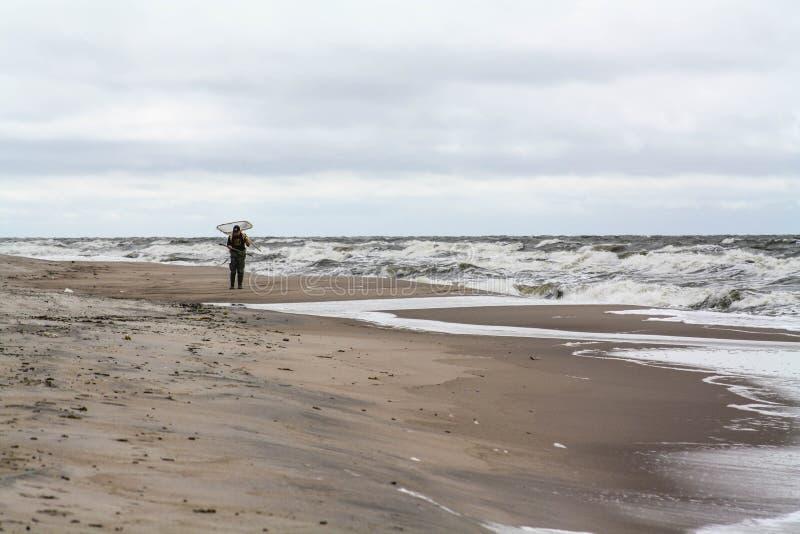 Homme seul sur la plage Rassemblement ambre, temps orageux images libres de droits