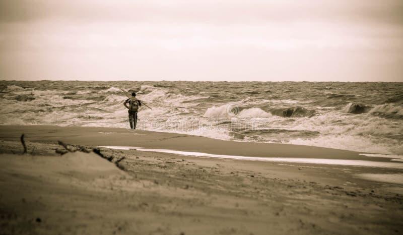 Homme seul sur la plage Rassemblement ambre, temps orageux photo libre de droits