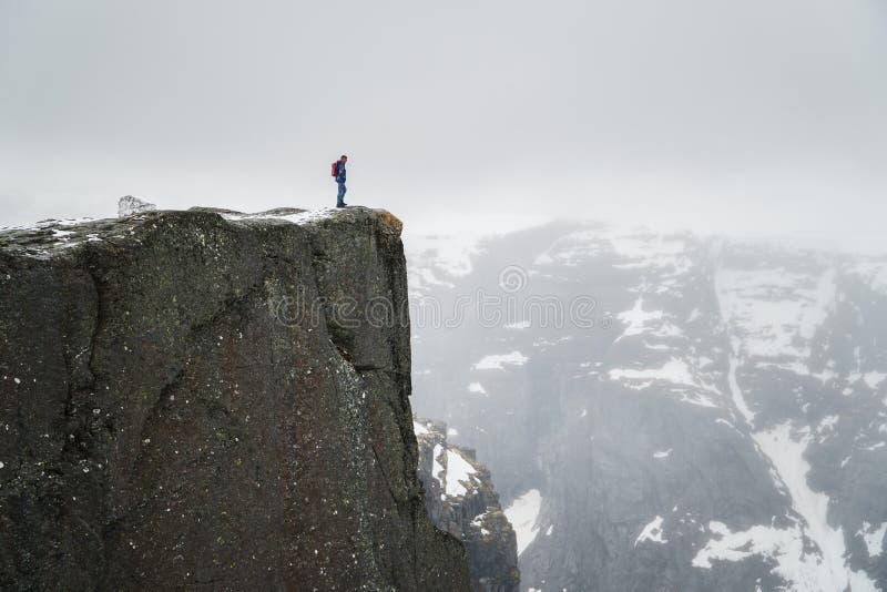 Homme seul sur la roche, position de voyageur sur le bord élevé de la falaise et de regarder des montagnes en brume photographie stock libre de droits