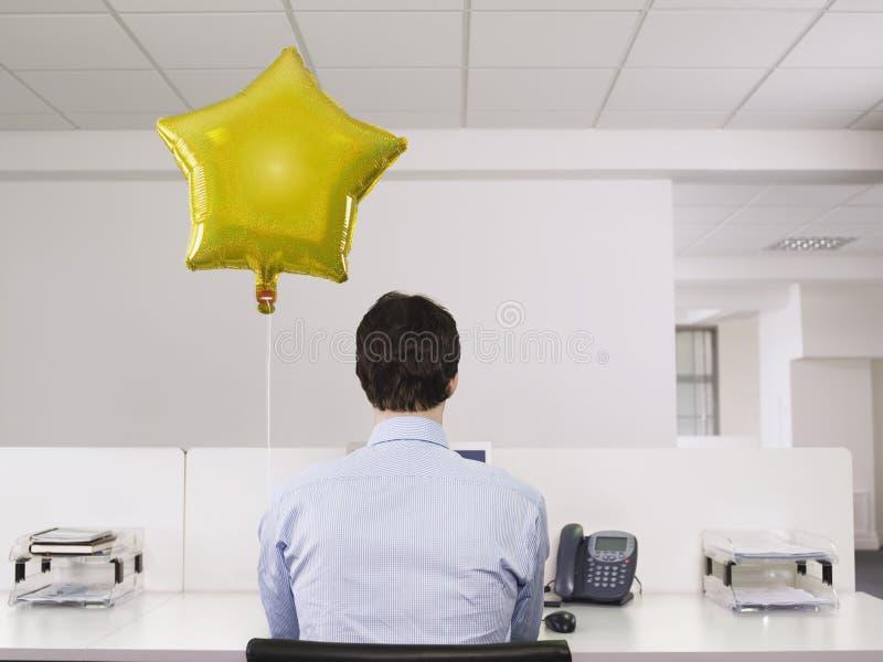 Homme seul travaillant près du ballon dans le bureau images stock