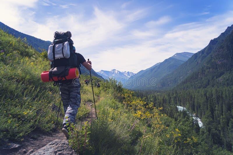 Homme seul trimardant aux montagnes de coucher du soleil avec des vacances d'été lourdes de concept d'aventure d'envie de voyager photos libres de droits