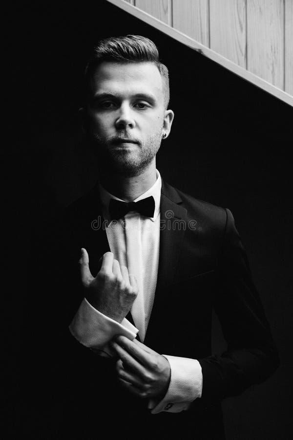 Homme sexy dans la pose de smoking et de noeud papillon image libre de droits